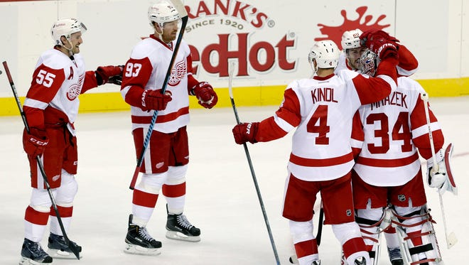 Detroit Red Wings goalie Petr Mrazek (34), of the Czech Republic, is congratulated by teammates after making three saves in a shootout to give his team a 5-4 win over the New Jersey Devils in an NHL hockey game, Friday, Nov. 28, 2014, in Newark, N.J.