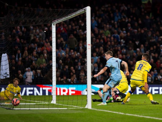 Manchester City's James Milner, centre right in blue, scores his second goal as his team beat Sheffield Wednesday 2-1 during their English FA Cup third round soccer match at the Etihad Stadium, Manchester, England, Sunday, Jan. 4, 2015. (AP Photo/Jon Super)