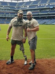 This photo provided by Earl Granville shows Granville posing with Alex Douglass, right, poses with Earl Granville at Citizens Bank Park in Philadelphia in Sept. 2018. Douglas, the Pennsylvania state police trooper who was shot in a 2014 ambush has had his right leg amputated below the knee. Granvillle is a veteran who lost his leg in 2008 when his vehicle hit a roadside bomb in Afghanistan. An acquaintance connected the two when Douglass expressed interest in doing a marathon, knowing Granville had completed several since being wounded. (Earl Granville via AP)