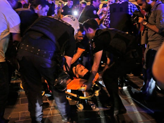 An injured man is attended by police when Turkish forces soldiers opened fire to disperse the crowd in Istanbul's Taksim square, early Saturday, July 16, 2016. Members of Turkey's armed forces said they had taken control of the country, but Turkish officials said the coup attempt had been repelled early Saturday morning in a night of violence, according to state-run media.