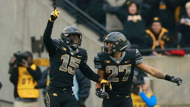 Iowa defensive backs Joshua Jackson (15) and Amani Hookier (27) combined for four interceptions against Ohio State on Saturday.