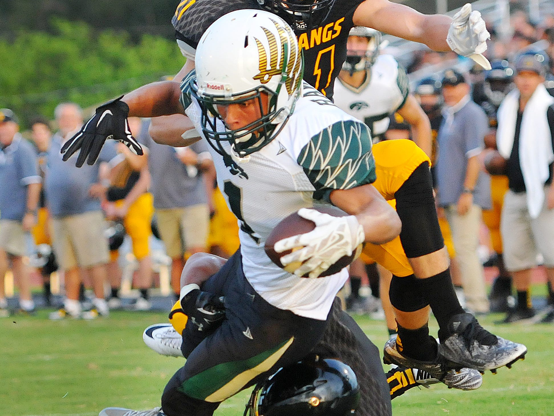 Viera High's Travis Jones (1) dives over Merritt Island High defenders for a first quarter touchdown during Friday night's game held at Mustang Stadium.