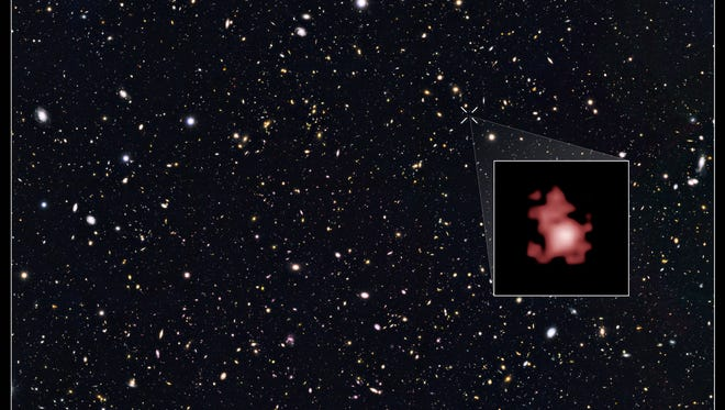 This image provided by the Space Telescope Science Institute, taken with the Hubble Space Telescope, shows a hot, star-popping galaxy that is far, far away, farther than any previously detected, from a time when the universe was a mere toddler of about 400 million years old.