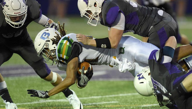 Belhaven receiver LaMiquell Roberts dives for yards after a catch between three Millsaps defenders on Thursday.