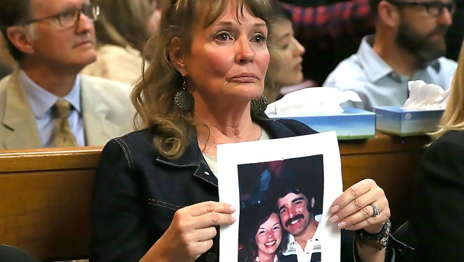 An attendee at the arraignment of Joseph DeAngelo, the accused Golden State Killer, holds a photo of Cheri Domingo and her boyfriend Gregory Sanchez, who were killed in 1981.
