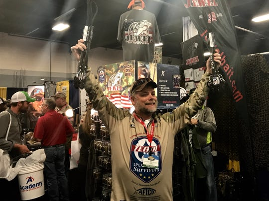 A hawker holds up items for sale at the Bassmaster expo Saturday.