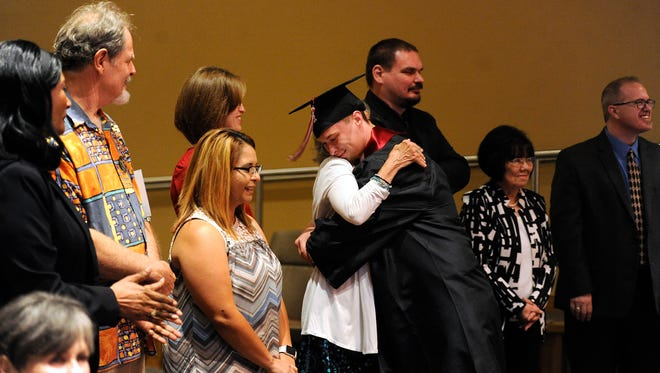 Premier High School graduate Logan Wilson gets a hug from a teacher after walking across the stage during Premier's graduation ceremony on Friday, June 2, 2017, at Highland Church of Christ.