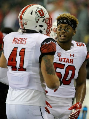 Utah defensive end Pita Taumoepenu, right, talks with linebacker Jared Norris (41) on the sideline during the first half of an NCAA college football game against Washington, Saturday, Nov. 7, 2015, in Seattle.