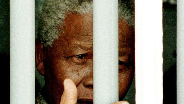 In this file photo, Nelson Mandela stands on March 27, 1998 behind the bars of the former cell where he spent 18 of his 27 years as a political prisoner on Robben Island.