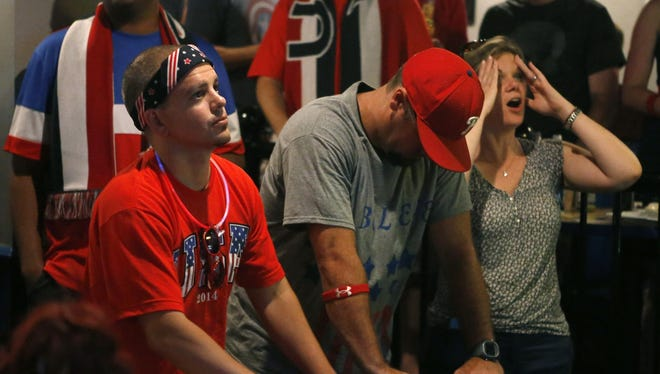 Fans - including Dave Redfield (front, from left) of Carneys Point, New Jersey, Bill Clouser of Elkton, Maryland, and Erika Murphy of Wilmington react at C.R. Hooligan's in Wilmington after Belgium got on the board in extra time during Team USA's loss to Belgium in the World Cup on Tuesday evening.