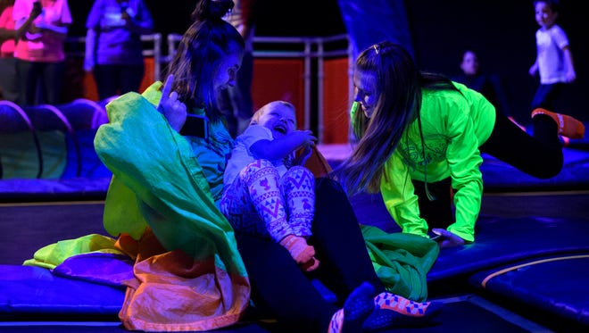 Tiffany Singer (left) and Shea Singer (right) share a laugh with Emma Ditmore, 2, as they play peekaboo with a rainbow parachute during the Toddler Time GLOW Jump at Sky Zone in Evansville, Ind., Sunday, Dec. 31, 2017. They traveled from Jasper, Ind., to jump on the trampolines under glowing black lights. Sky Zone holds Toddler Time, for children old enough to walk through 5 years of age, every Sunday from 10 a.m to noon.