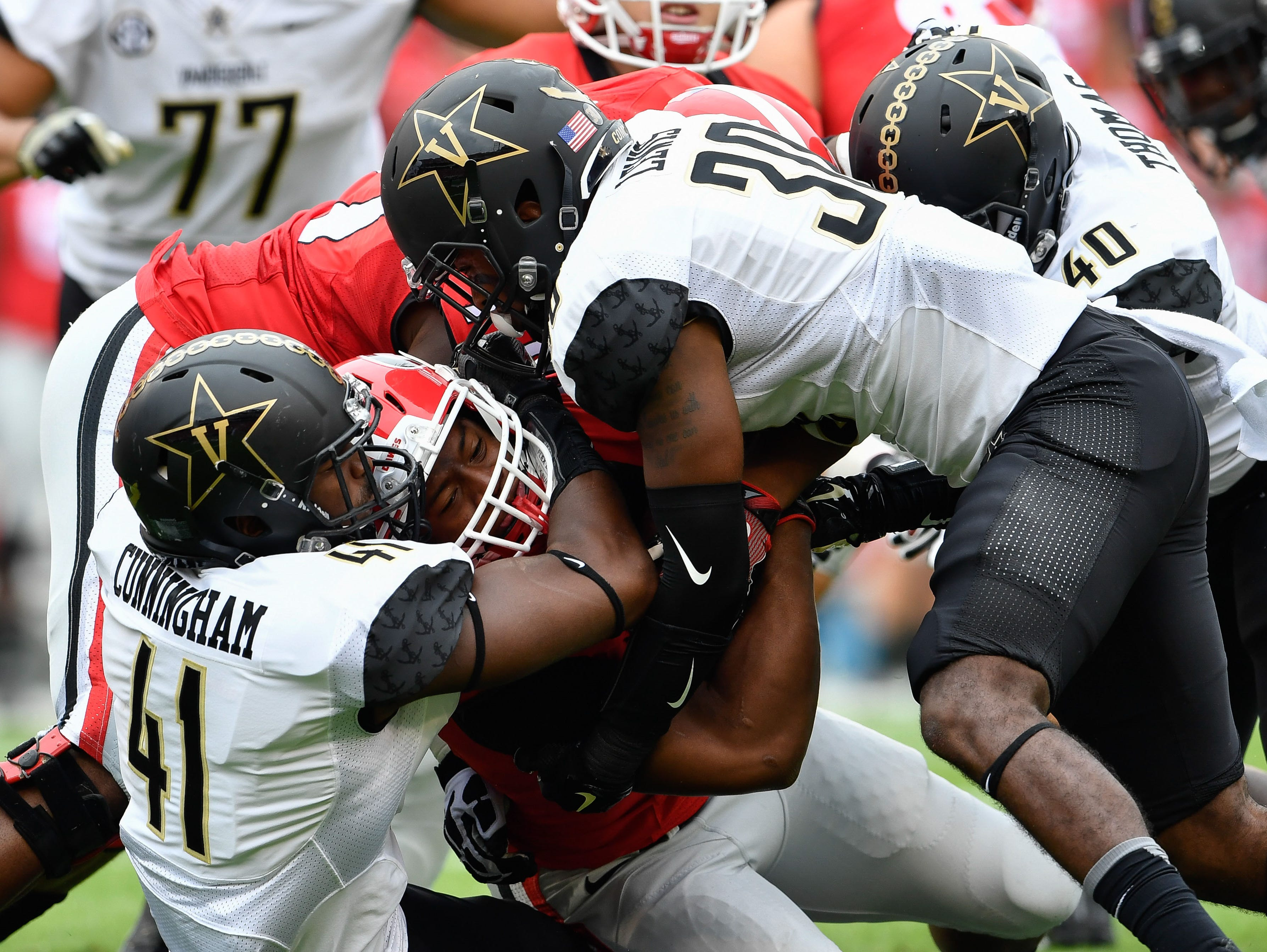 Georgia running back Nick Chubb (27) is tackled by Vanderbilt linebacker Zach Cunningham (41) and defensive back Bryce Lewis (30) during the first quarter last season.