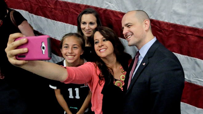 Supporters Alexa Herrera, 12, left, and her mother Jeanette Herrera, center, pose for a photo with Independent presidential candidate Evan McMullin, right, following a rally Friday, Oct. 21, 2016, in Draper, Utah.