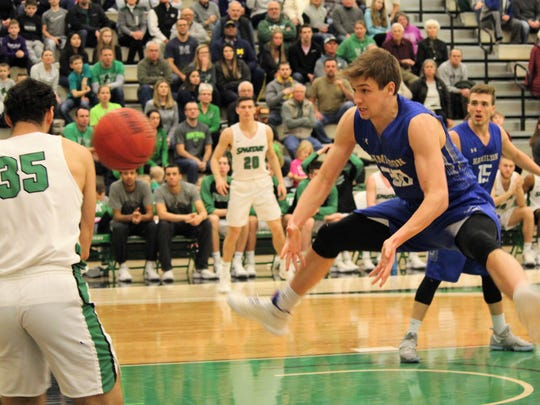 Hamilton College's Peter Hoffmann tries to get out of the way as York College's Blayde Reich, left, attempts to retain possession by throwing the ball off Hoffmann during Saturday's NCAA Division III men's basketball tournament second-round game in York.
