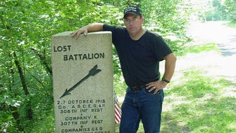 """Robert Laplander stands next to a marker at the site in France where the 77th Regiment's Lost Battalion held out for four days while surrounded by German troops during the World War I Battle of the Meuse-Argonne. Laplander is an expert on the Lost Battalion, wrote a book about the doomed unit and is featured in a three-part """"American Experience"""" series on World War I airing on PBS April 10-12."""