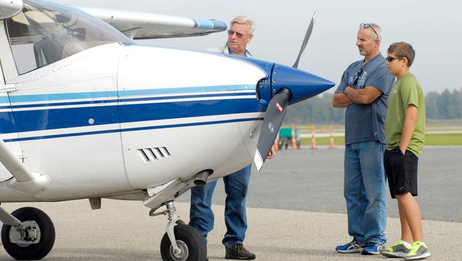 Gary Monarch, and his son Bradley, 13, of China Township, listen to pilot, Robert Thoms, as he talks about his airplane, Sunday, Sept. 28 during Airport Day at the St. Clair County Airport.