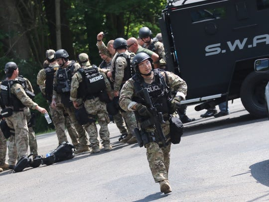 The SWAT team assembles at Rummel and Mansfield-Lucas roads on the afternoon of July 25, as the search continued for Amber Alert suspect Robert Beane.