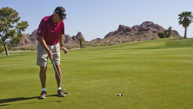 Bruce Ainsworth, Gilbert, watches his putt go in on the first hole at Papago Golf Course, Thursday, May 8, 2014.