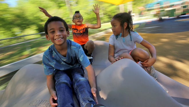 From left, Khadyn Daniels, Bryan Ross Jr., and Kierra Ross play at the Holly Oak Park playground after renovation of the playground in 2019.