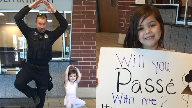 Vayda Ojeda, 4, performes a passe, with an officer of the Greenfield Police Department.