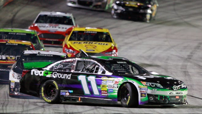 Driver Denny Hamlin (11) gets turned by driver Kevin Harvick, behind, as they come down the front straight away during a NASCAR Sprint Cup Series auto race at Bristol Motor Speedway on Saturday, Aug. 23, 2014, in Bristol, Tenn.