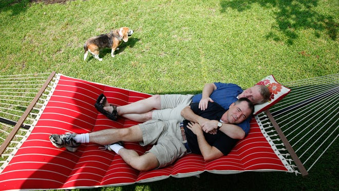 Mark Phariss and Vic Holmes of Plano, Texas, relax on a hammock while they enjoy a Saturday at their lake house in Gun Barrel City, Texas.