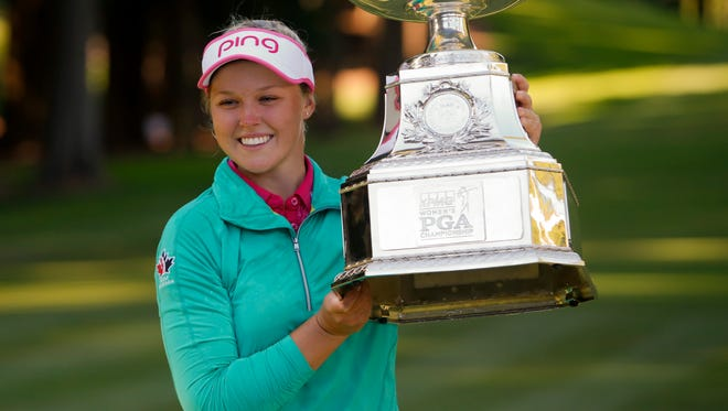 Jun 12, 2016; Sammamish, WA, USA; Brooke Henderson holds the KPMG Women's PGA Championship Trophy after winning in a play off following the final round at Sahalee Country Club - South/North Course.