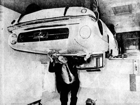 Chester Weedon stands under the Ford Mustang fastened