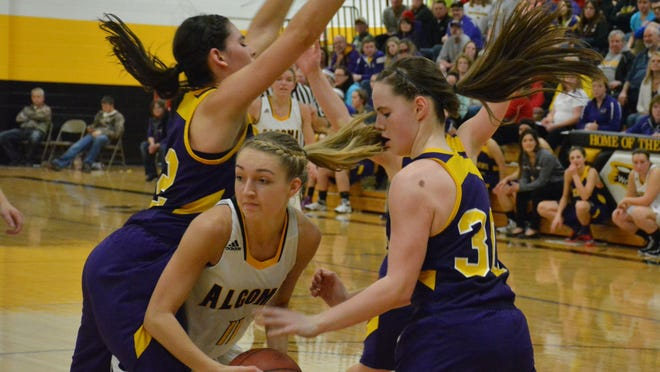 Algoma's Corrina Dart looks for a way around Kewaunee's Brooke Geier and Ellie Olsen during the Wolves' home game Dec. 23.