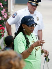 Pastor Sandra Ben talks to participants as she leads a community walkabout from her Safe United Neighborhoods on Friday.