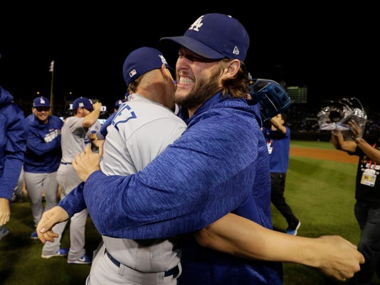 Los Angeles Dodgers' Enrique Hernandez and Clayton Kershaw celebrate after Game 5 of baseball's National League Championship Series against the Chicago Cubs, Thursday, Oct. 19, 2017, in Chicago. The Dodgers won 11-1 to win the series and advance to the World Series. (AP Photo/Matt Slocum)