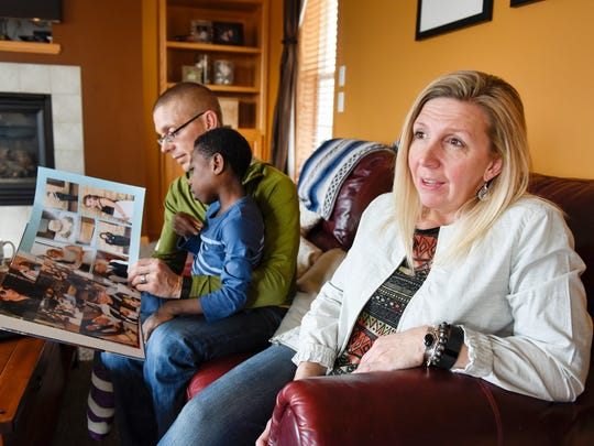 Jessica Neal talks about finally being able to bring home their adopted son Emmanuel, who is looking at family photos her her husband Jason Thursday, March 31, at their home in Andover. Emmanuel was adopted from Liberia but could not leave until after the Ebola outbreak. The Neals lived in Sartell when they started the adoption process.