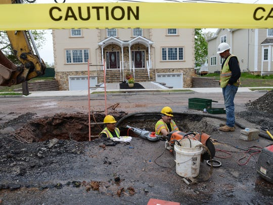 Passaic Valley Water Commission workers  at a water main break on Kipp Avenue in Lodi on April 27, 2016. Emergency repairs on a water main break often cost more in overtime and inconvenience.