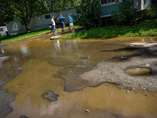 People stand near the scene of a water line that has