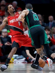 Portland Trail Blazers forward Trevor Ariza, left, and Boston Celtics forward Jayson Tatum collide during the first half of an NBA basketball game in Portland, Ore., Tuesday, Feb. 25, 2020. (AP Photo/Craig Mitchelldyer)