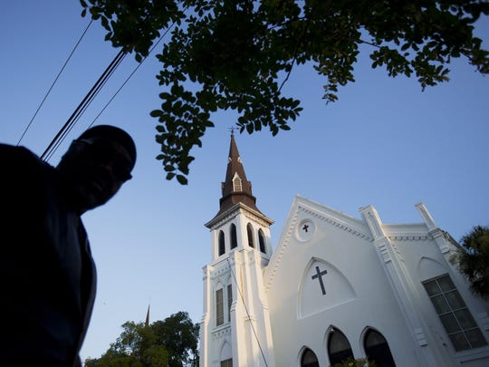Emanuel AME Church stands in the background as a mourner visits a sidewalk memorial in memory of the shooting victims Saturday, June 20, 2015, in Charleston, S.C.