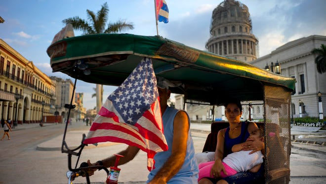 A taxi pedals his bicycle, decorated with Cuban and U.S. flags, as he transports a woman holding a sleeping girl near the Capitolio in Havana, Cuba, on March 15, 2016.