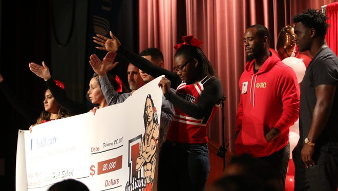 Students hold up a check made out to Immokalee High School for $20,000 in the school's auditorium on Wednesday. UnitedHealthcare, along with Immokalee grad Edgerrin James and Giants cornerback Dominique Rodgers-Cromartie, presented the school with a $20,000 check to help the athletic department recoup lost revenue due to Hurricane Irma.