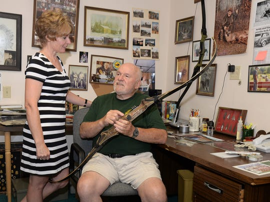 Gordon Bentley and his daughter, Lynn Stiklestad, admire one of his favorite recurve bows at his home office near Montello.