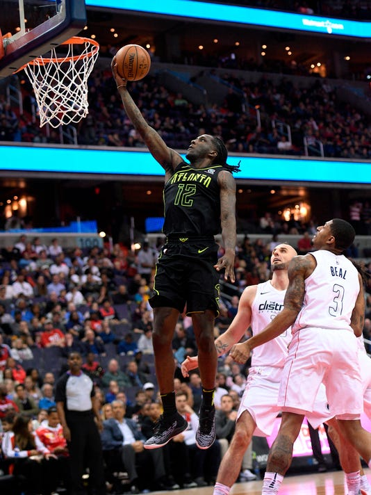 Atlanta Hawks forward Taurean Prince (12) goes to the basket past Washington Wizards guard Bradley Beal (3) and center Marcin Gortat, center, of Poland, during the first half of an NBA basketball game Friday, April 6, 2018, in Washington. (AP Photo/Nick Wass)