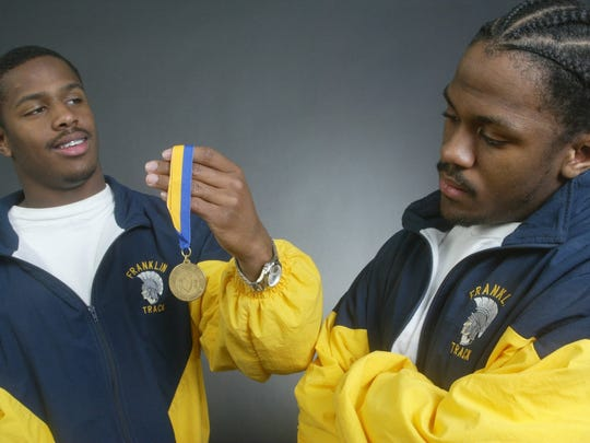 Franklin High School track star Jeff Porter (left) holds up a Meet of Champions gold medal in front of brother Joe Porter in 2003.
