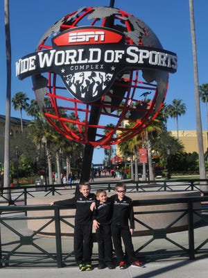 The Buffington brothers standing in front of the ESPN Wide World of Sports statue in Florida.