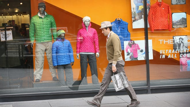 A shopper walks past a window display at a North Face store along the Magnificent Mile shopping district in Chicago. Retailers like The North Face use syndicated reviews to increase the product reviews on their site.