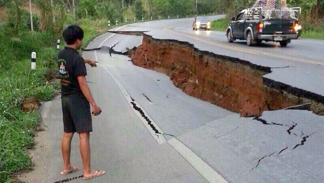 A man points at a damaged road following a strong earthquake May 5 in Chiang Rai province, northern Thailand.