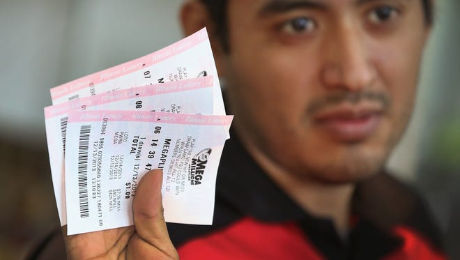 Roberto Fuentes prints up Mega Millions lottery tickets for a customer at a 7-Eleven store on Dec. 13 in Chicago.