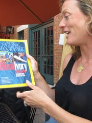 """Ashley Prout McAvey of Shelburne holds a copy of National Geographic Magazine featuring """"blood ivory"""" — a burgeoning illegal trade that has resulted in the slaughter of African elephants for their tusks."""