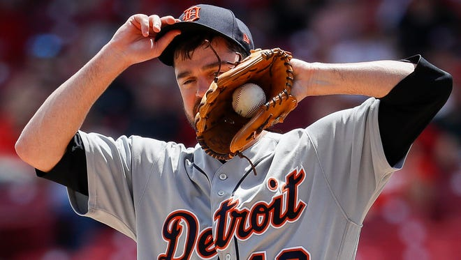 Tigers pitcher Louis Coleman wipes sweat from his face in the seventh inning of the Tigers' 5-3 loss to the Reds on Wednesday, June 20, 2018, in Cincinnati.
