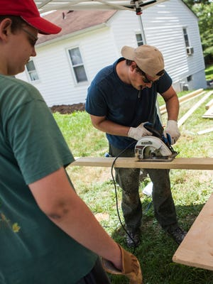 Philip Holbrook, with Renewing Homes of Greater Augusta, works under the shade of a tent while helping to rebuild a blind Staunton resident's damaged walkway on Tuesday, June 16, 2015.