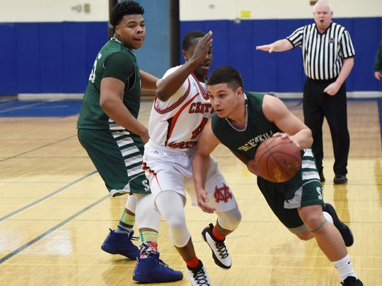 Spackenkill's Camron Abalos, right, takes the ball down the court during Saturday's Class B regional final game against Center Moriches at Suffolk County Community College in Selden.