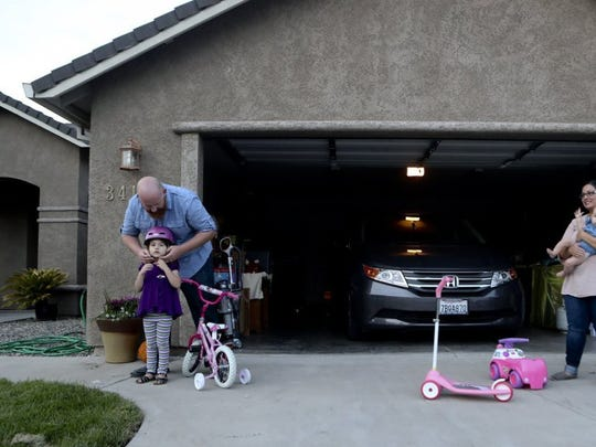 Enterprise football coach Russell McWilliams (left) puts a bike helmet on his daughter Rachel, 4, while his wife Vanessa holds their daughter Sophia, 6 months, at their home in Anderson.